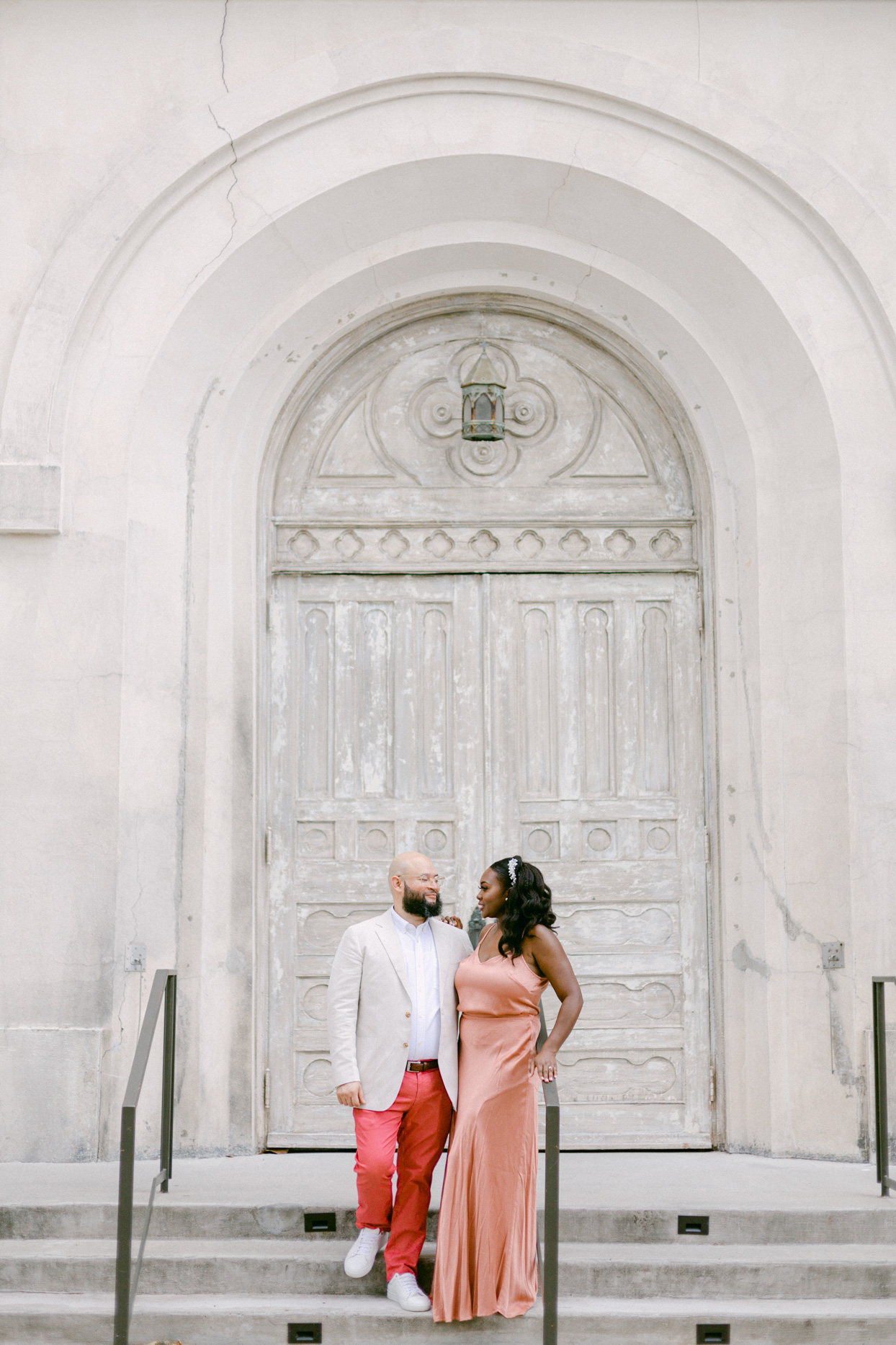 bride and groom in coral standing on steps