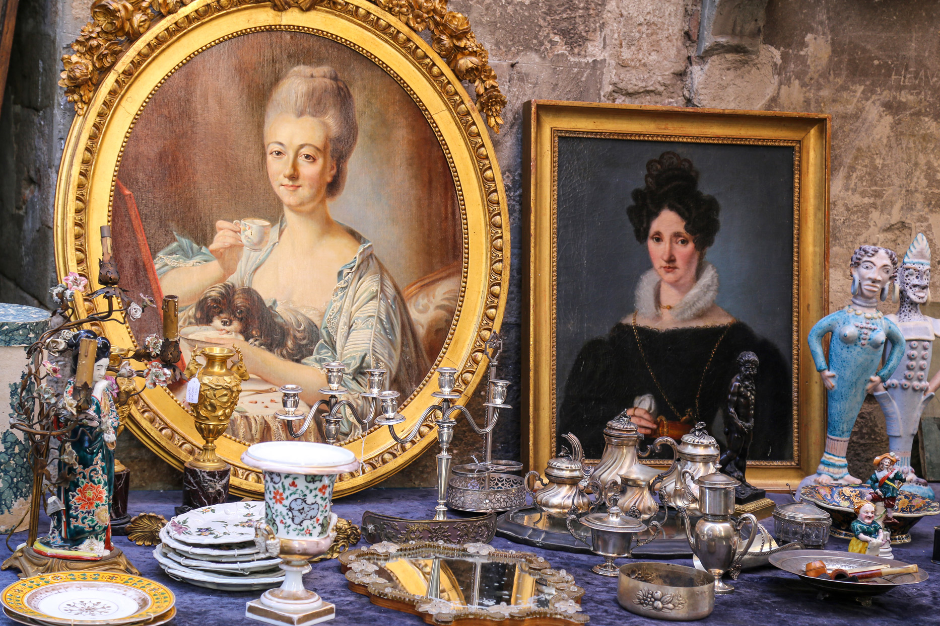 tabletop with antique paintings and serveware