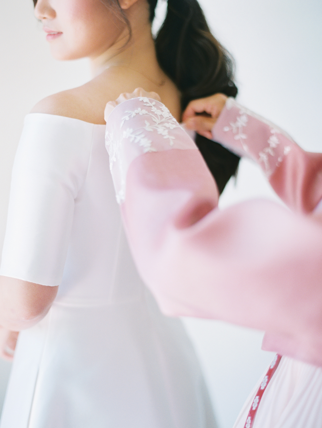 woman helping bride with wedding dress