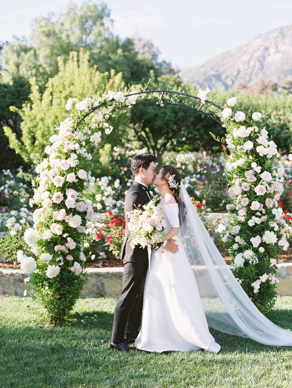 wedding couple first kiss under floral ceremony arch