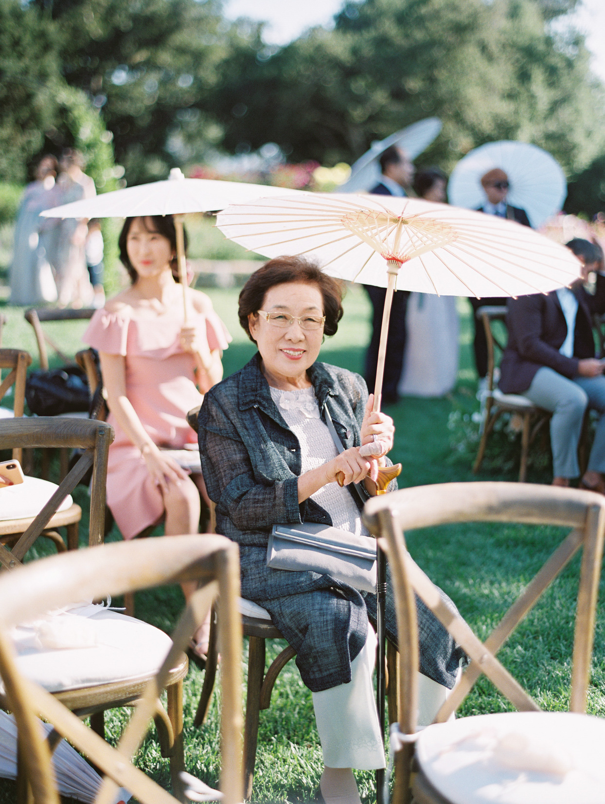 guests sitting on wooding ceremony seats holding parasols