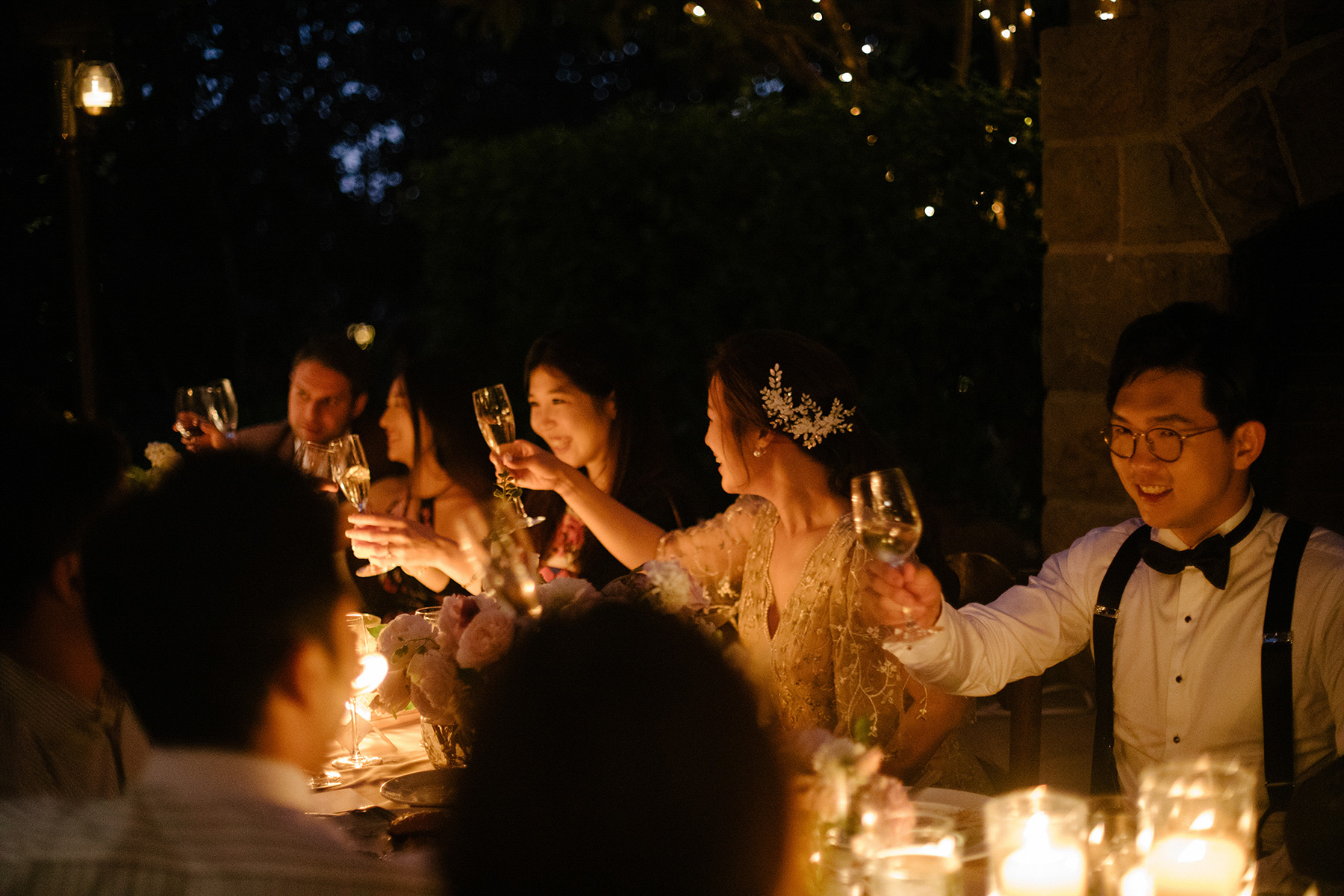 couple toasting champagne at candlelit reception