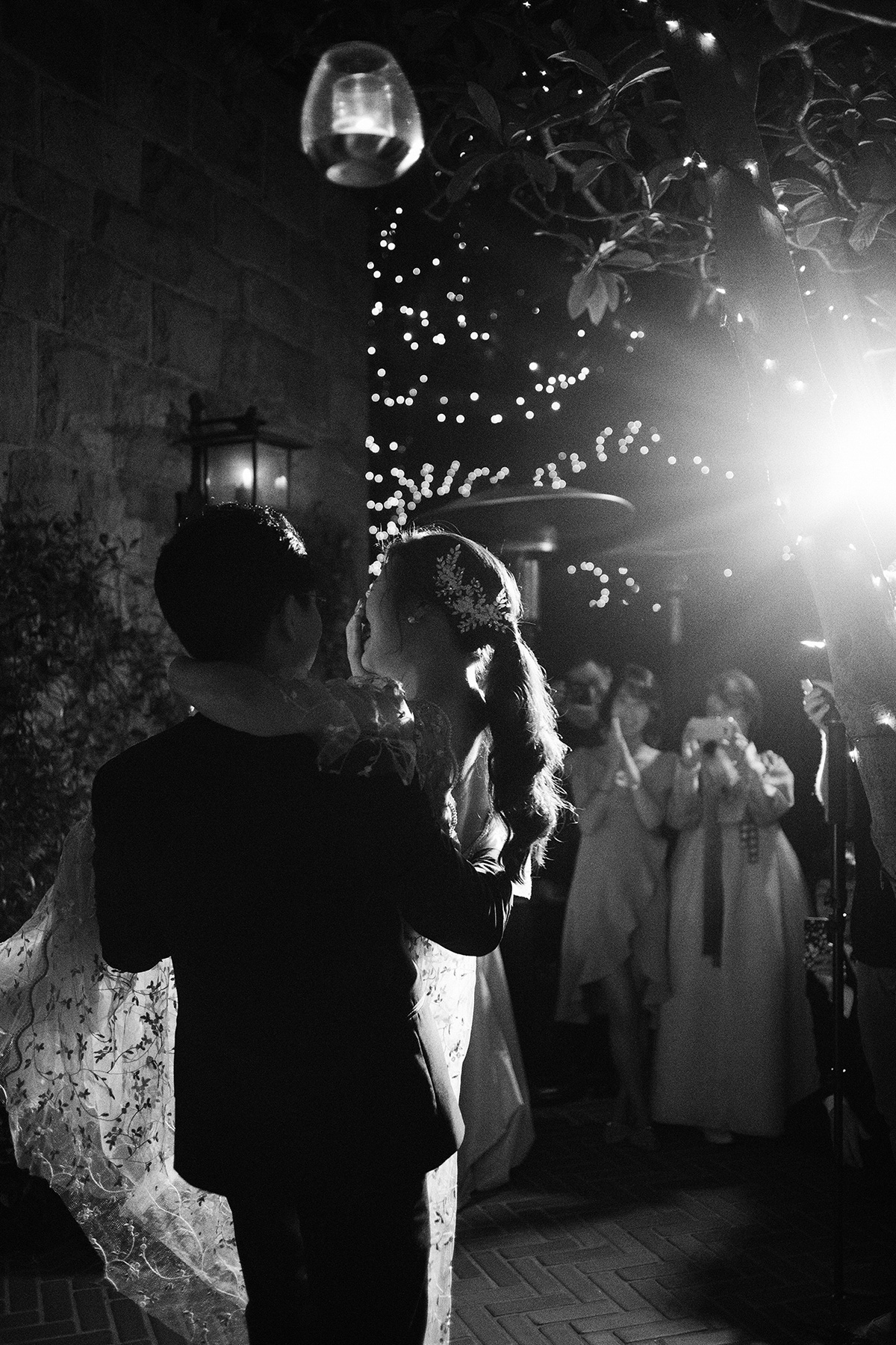 couple first dance at wedding reception under string lights
