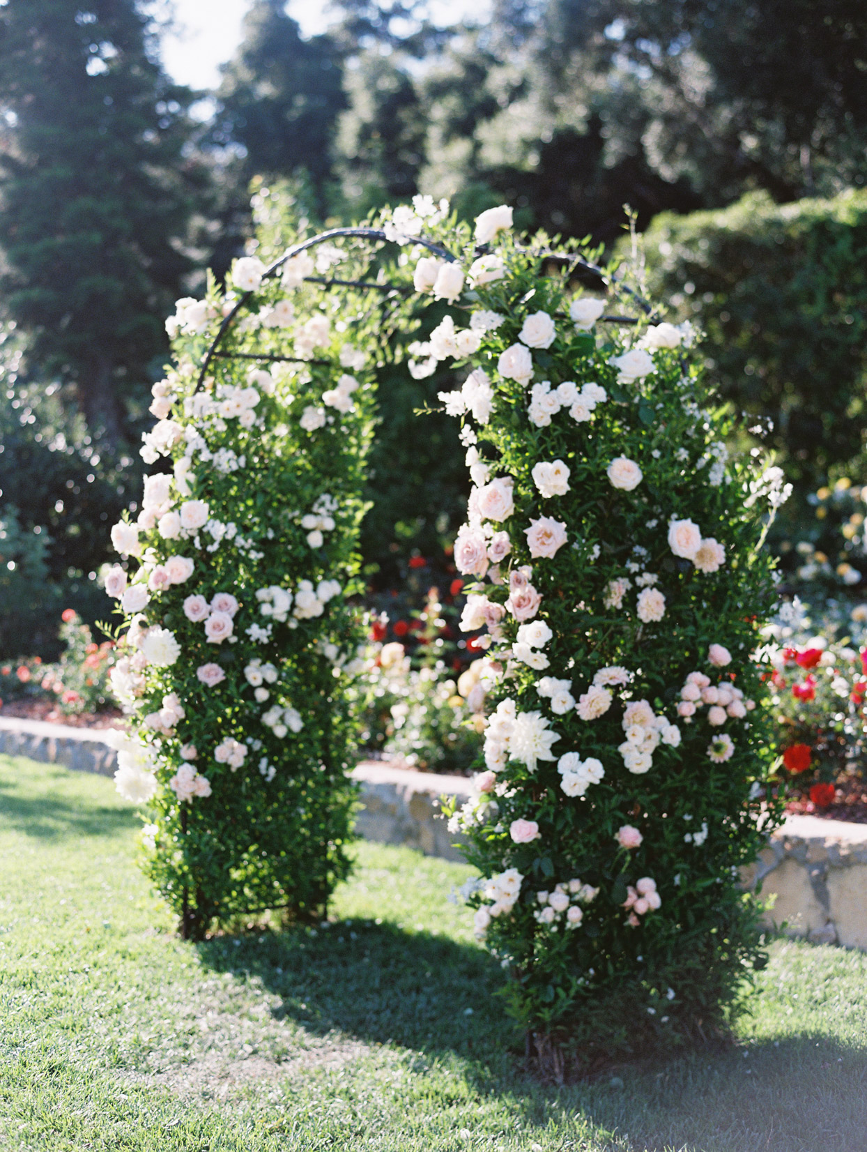 greenery and floral wedding ceremony arch in garden