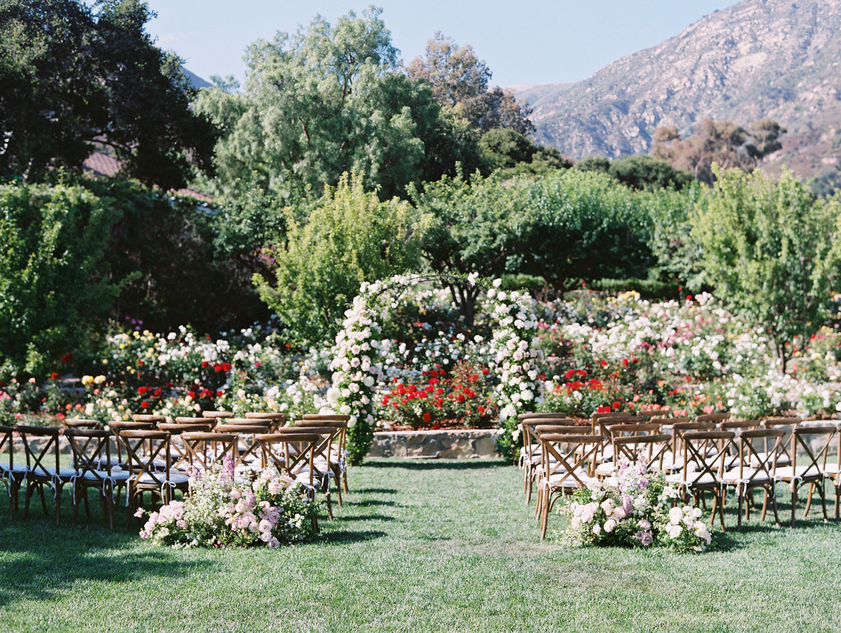outdoor wedding ceremony in garden filled with floral decor