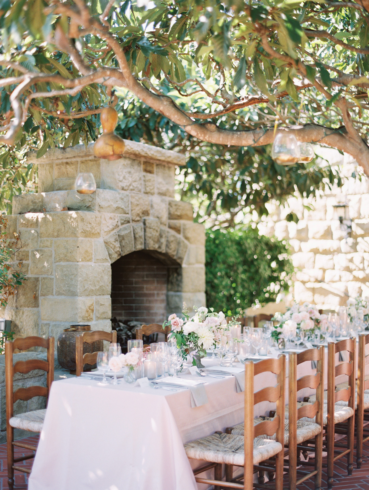 outdoor reception in elegant blush with greenery above tables