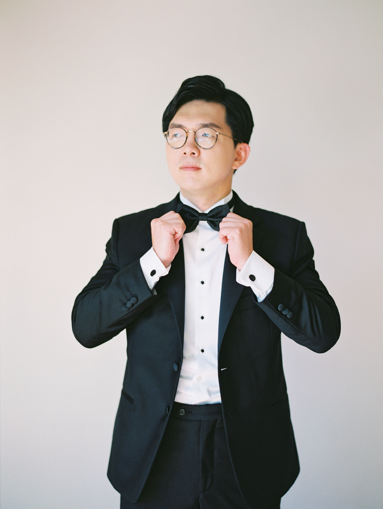 groom in black tux with bowtie and black cufflinks