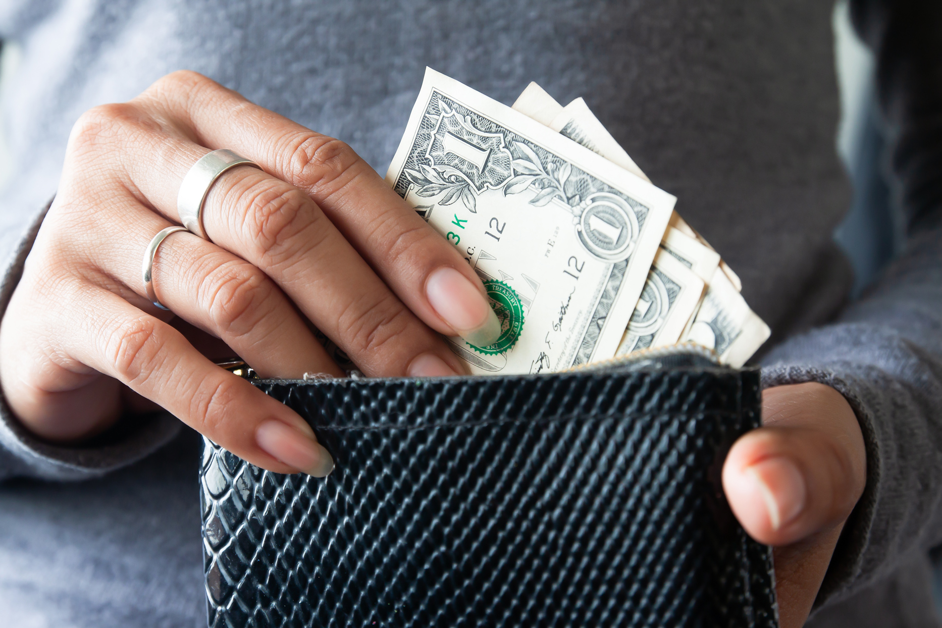 woman extracting one dollar bills from black wallet