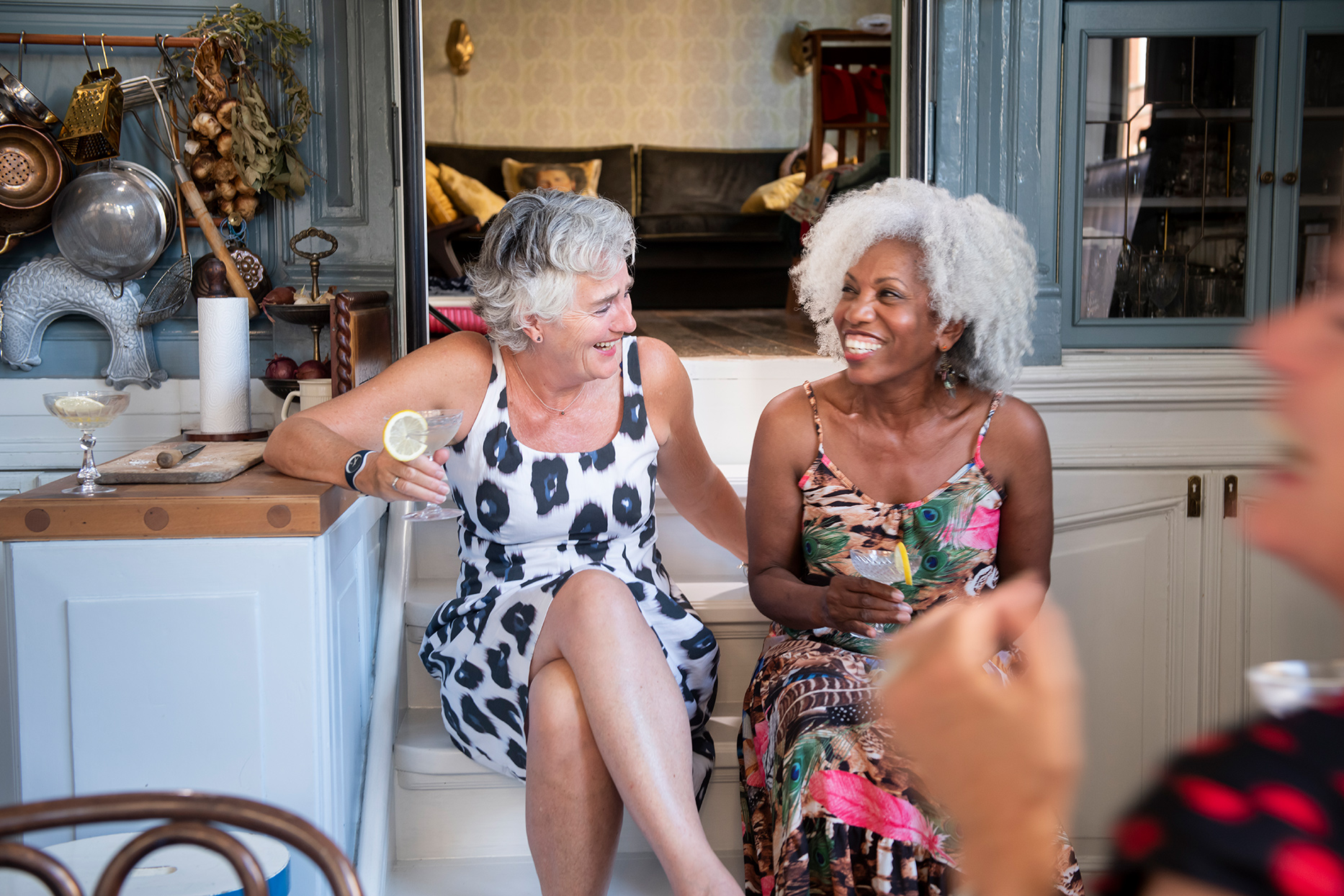 two woman sitting together laughing at cocktail party