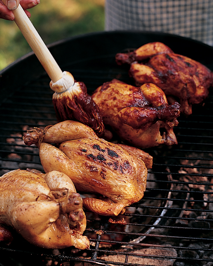whole chickens being brushed with barbecue sauce on a charcoal grill