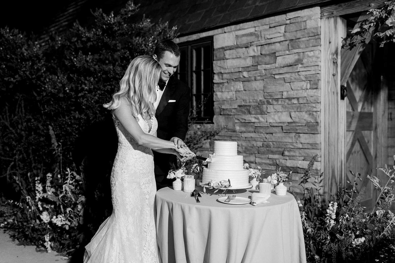 bride and groom cutting wedding cake outside