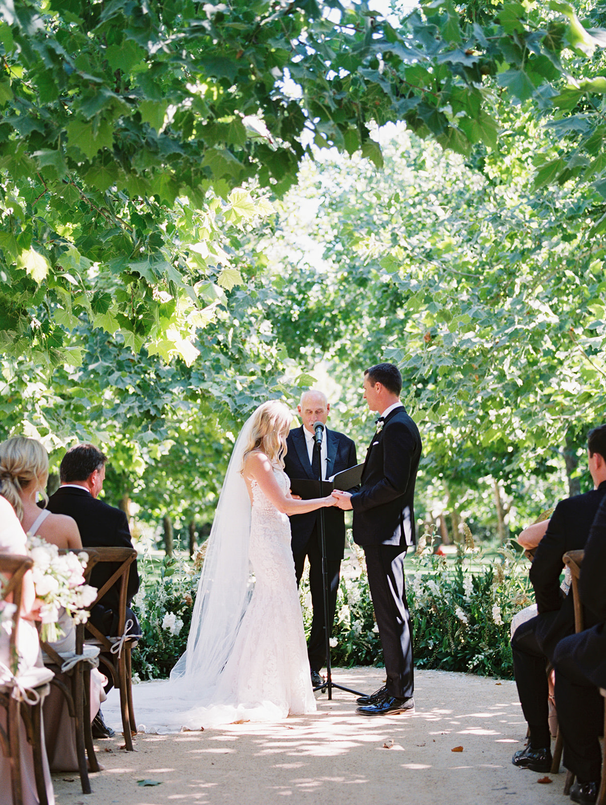 bride and groom holding hands during outdoor wedding ceremony