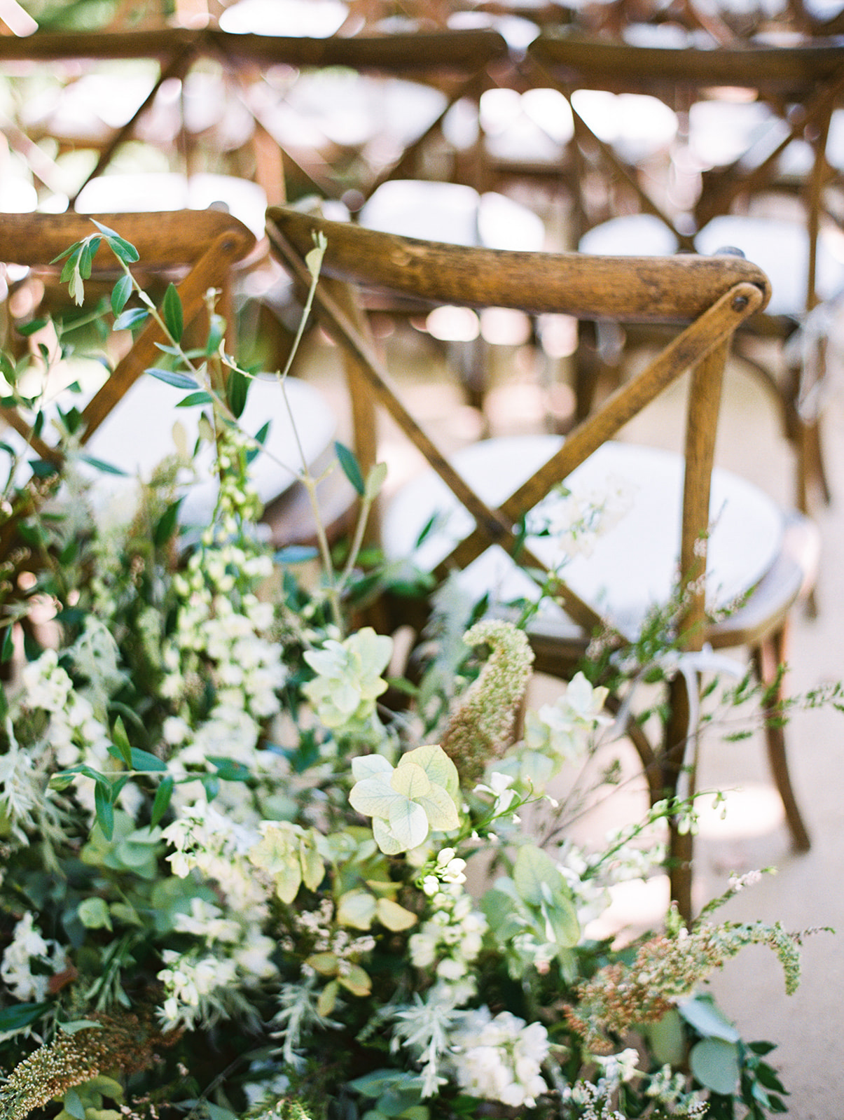 white floral bouquets with wedding ceremony chairs