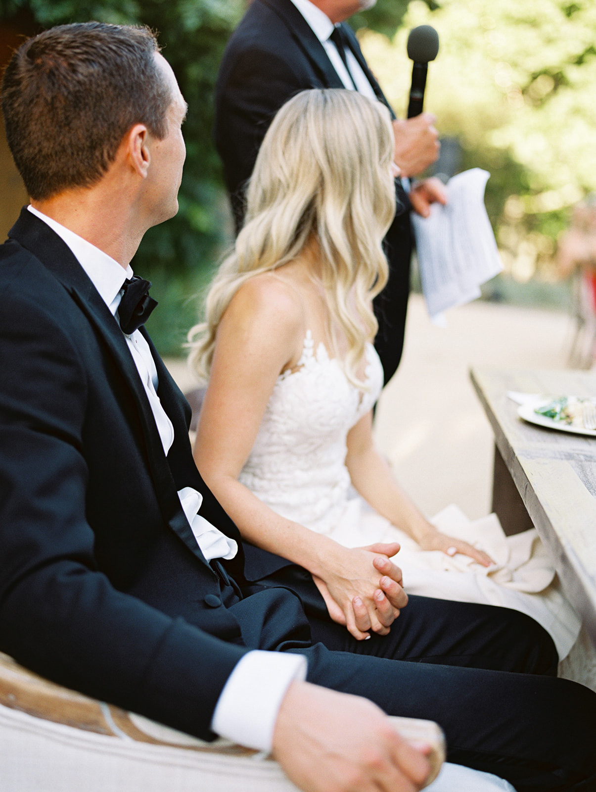 bride and groom sitting at sweetheart table holding hands