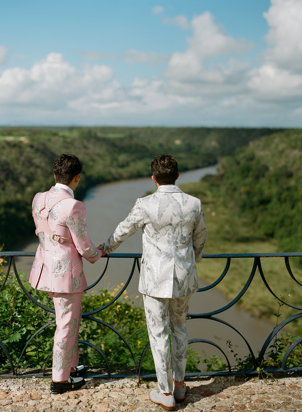 Grooms looking over water together