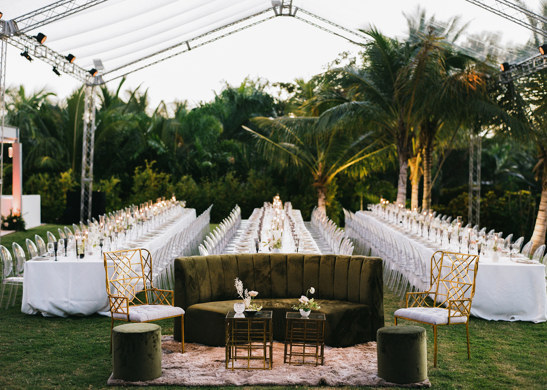 Wedding reception with three long tables with white linens and translucent chairs