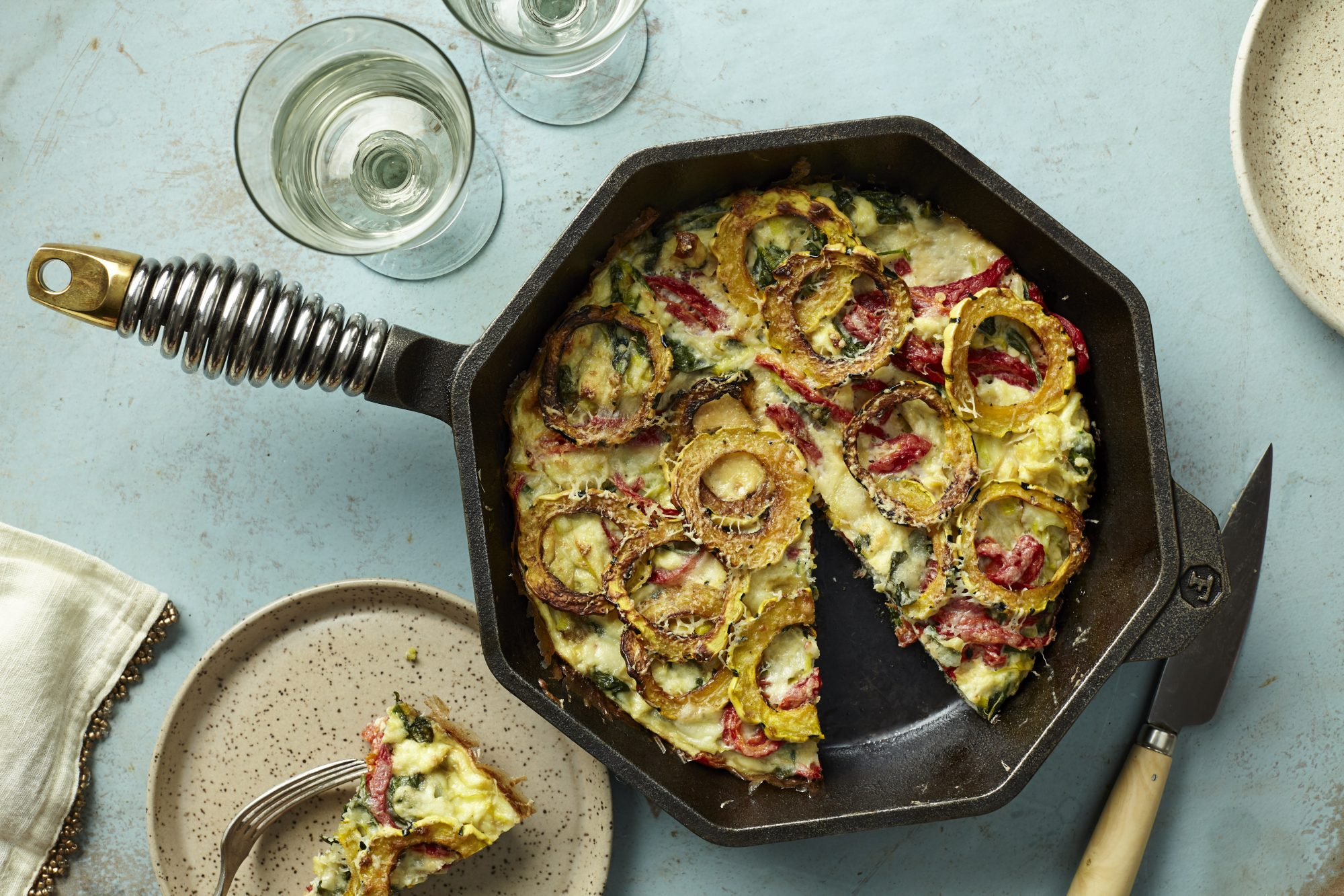 octagonal cast iron skillet holding a frittata on table
