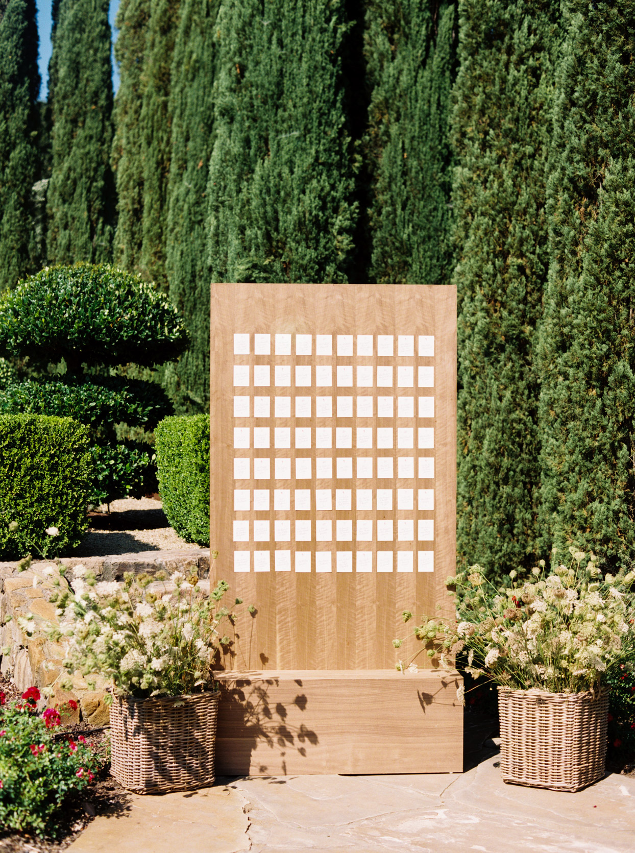 simple wooden board with escort cards in front of hedges