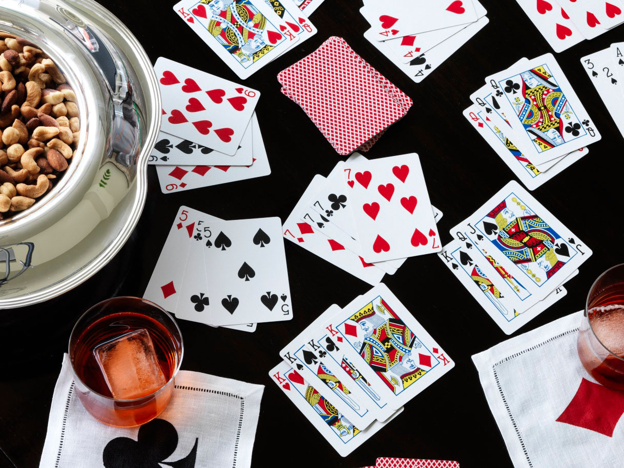 playing cards on black table with drinks and snacks