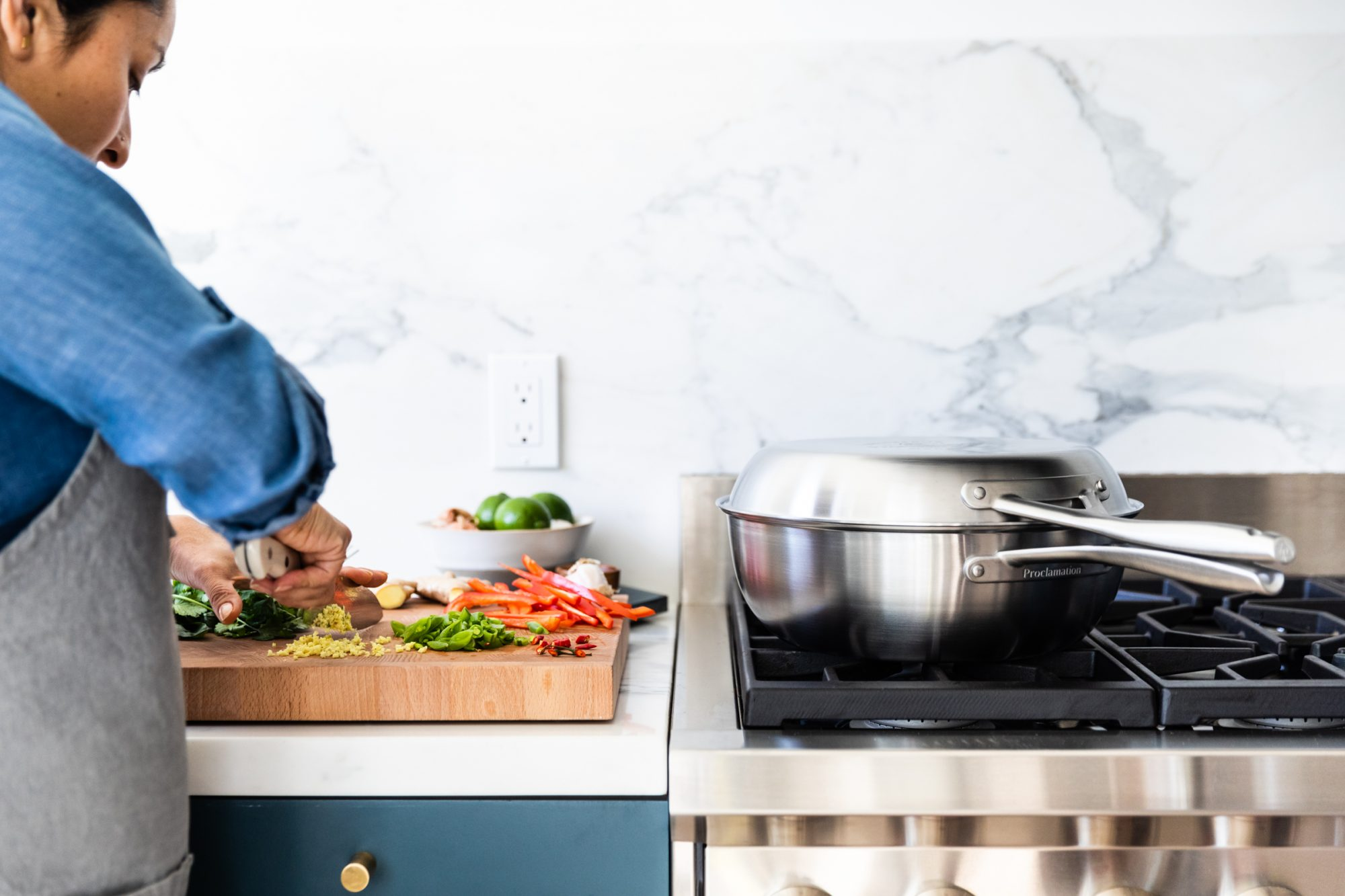 woman prepping vegetables beside stovetop with pans