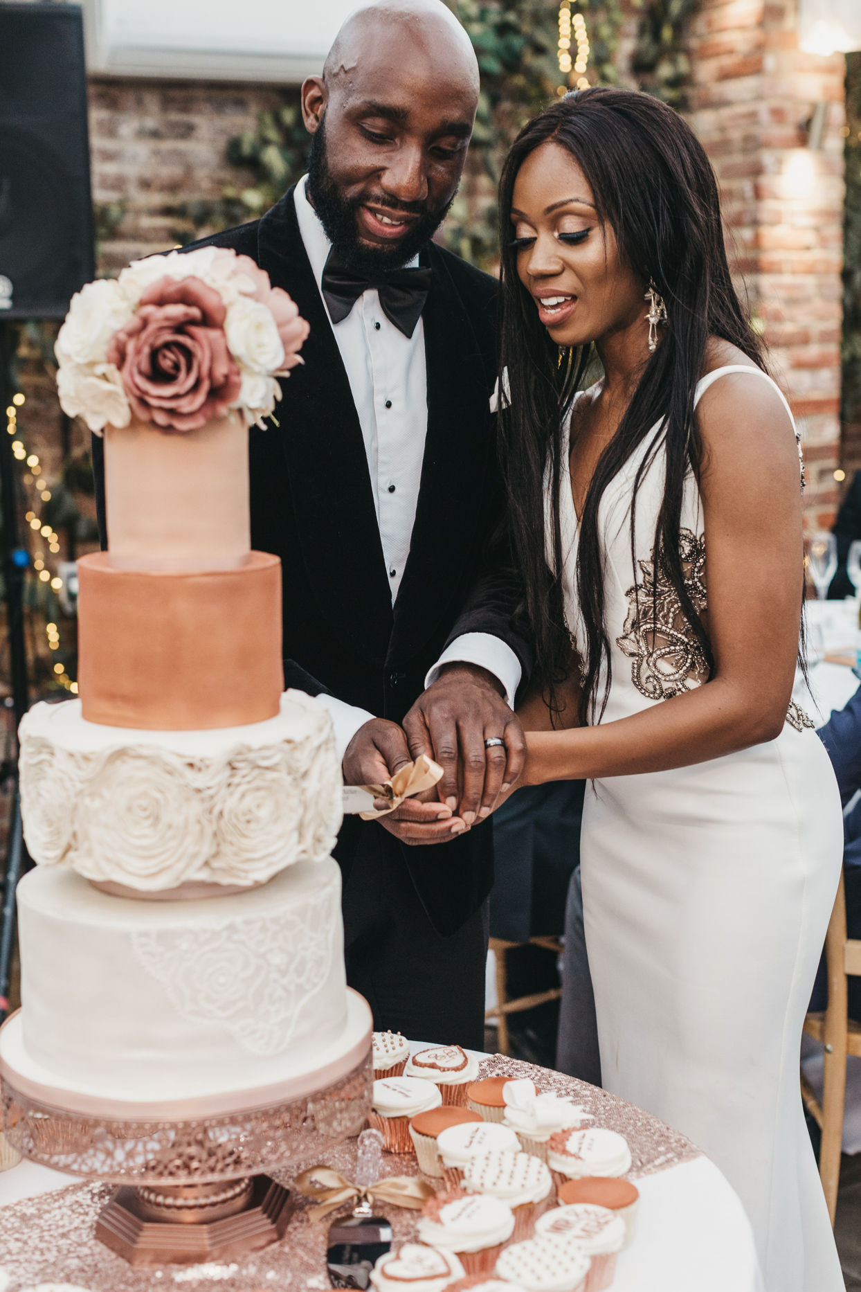 wedding couple slicing tiered cake