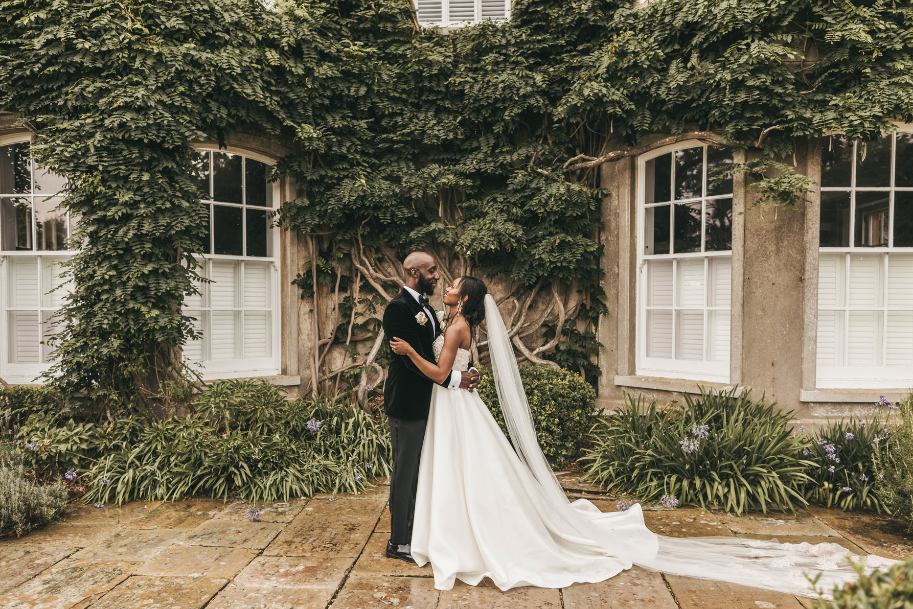 wedding couple holding each other outside historical property