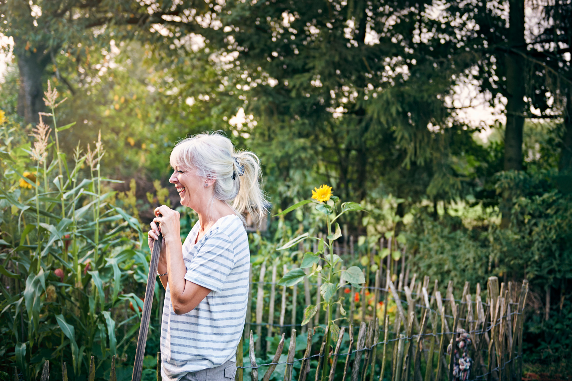 person laughing in garden holding gardening tool