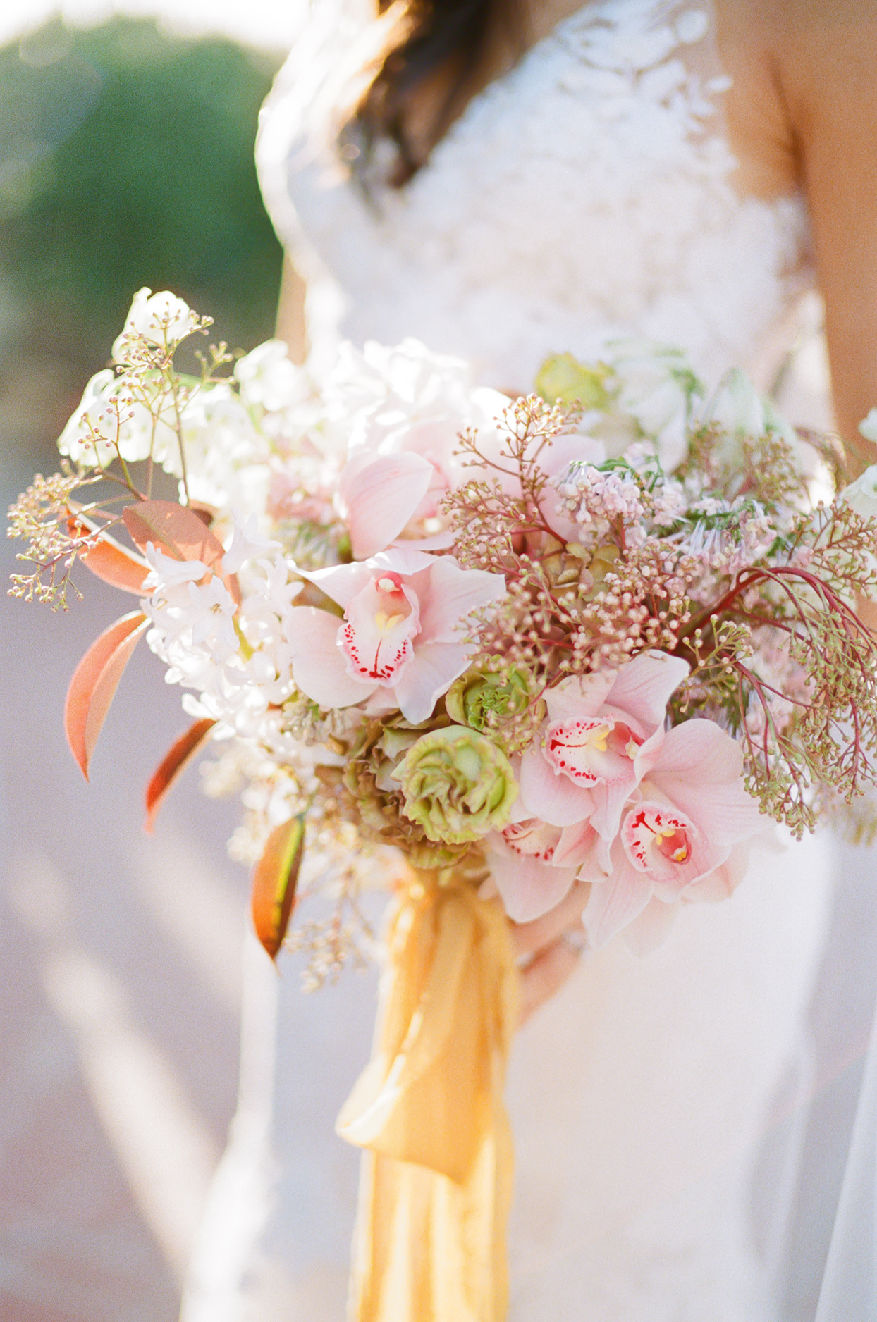loose and organic wedding bouquet of blooms in shades of white, cream, blush, and yellow