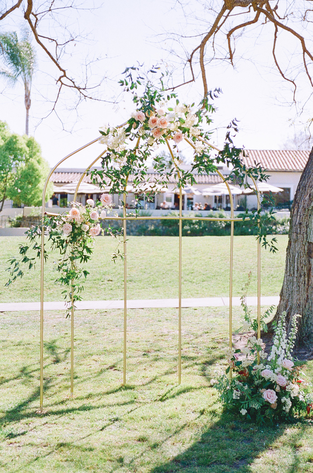 Outdoor wedding arch in a gold, birdcage-inspired style