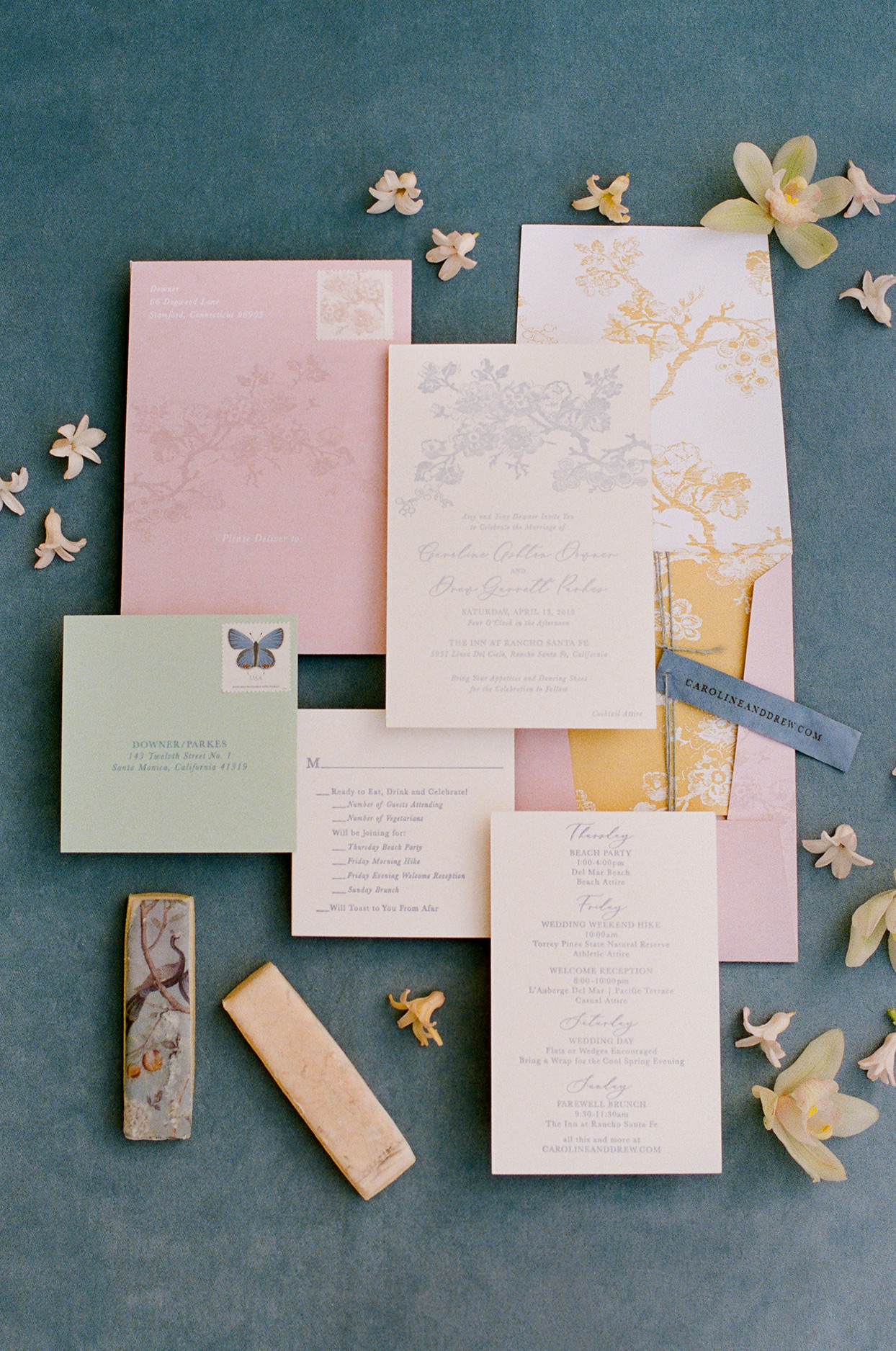 wedding invitation suite with a pastel color scheme with blue letterpress text on a white cotton paper card, a yellow chinois floral liner, and a custom-designed blush envelope