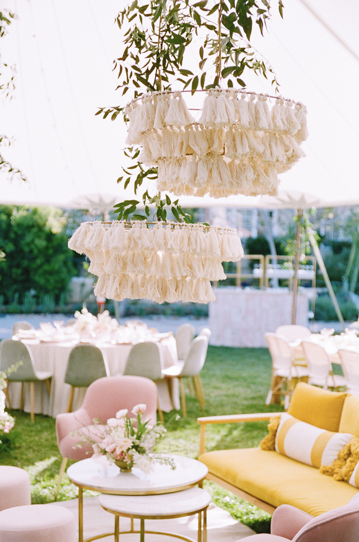 outdoor wedding lounge with pale ivory velvet linens and yellow chiffon runners