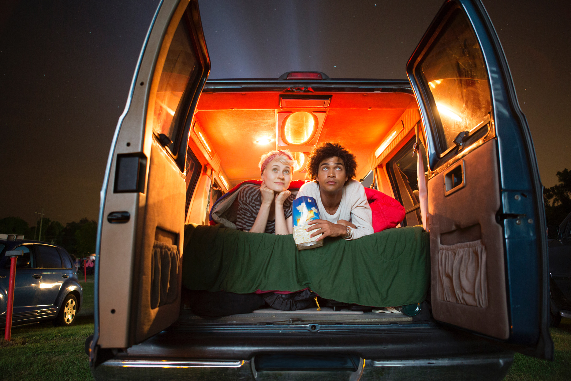 couple laying in back of van at drive in movie theater