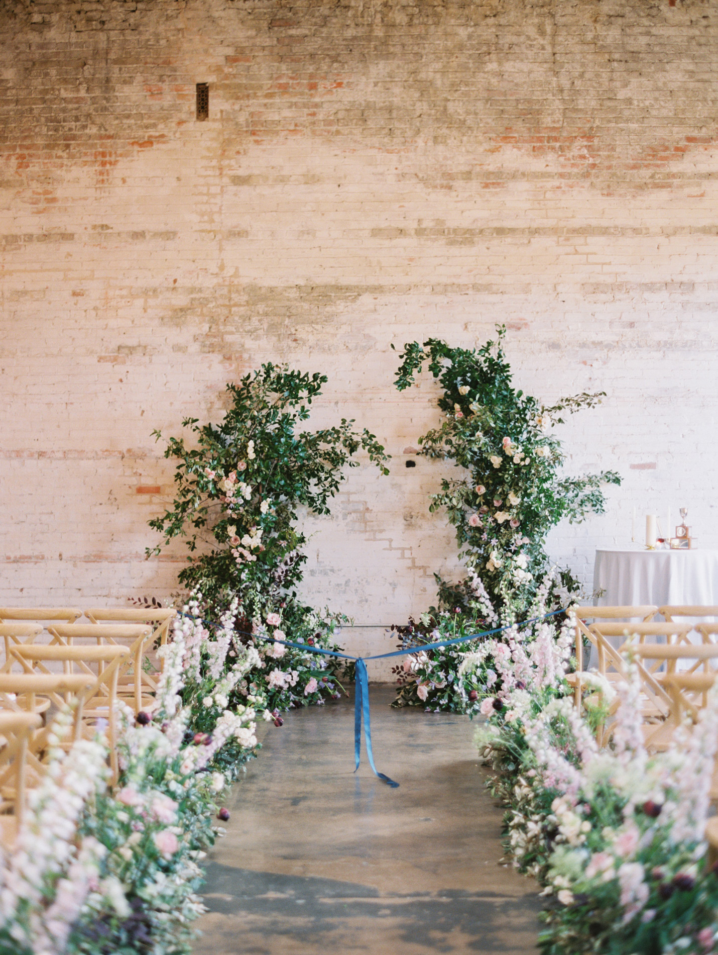 aisle decorated with flowers leading to floral arch