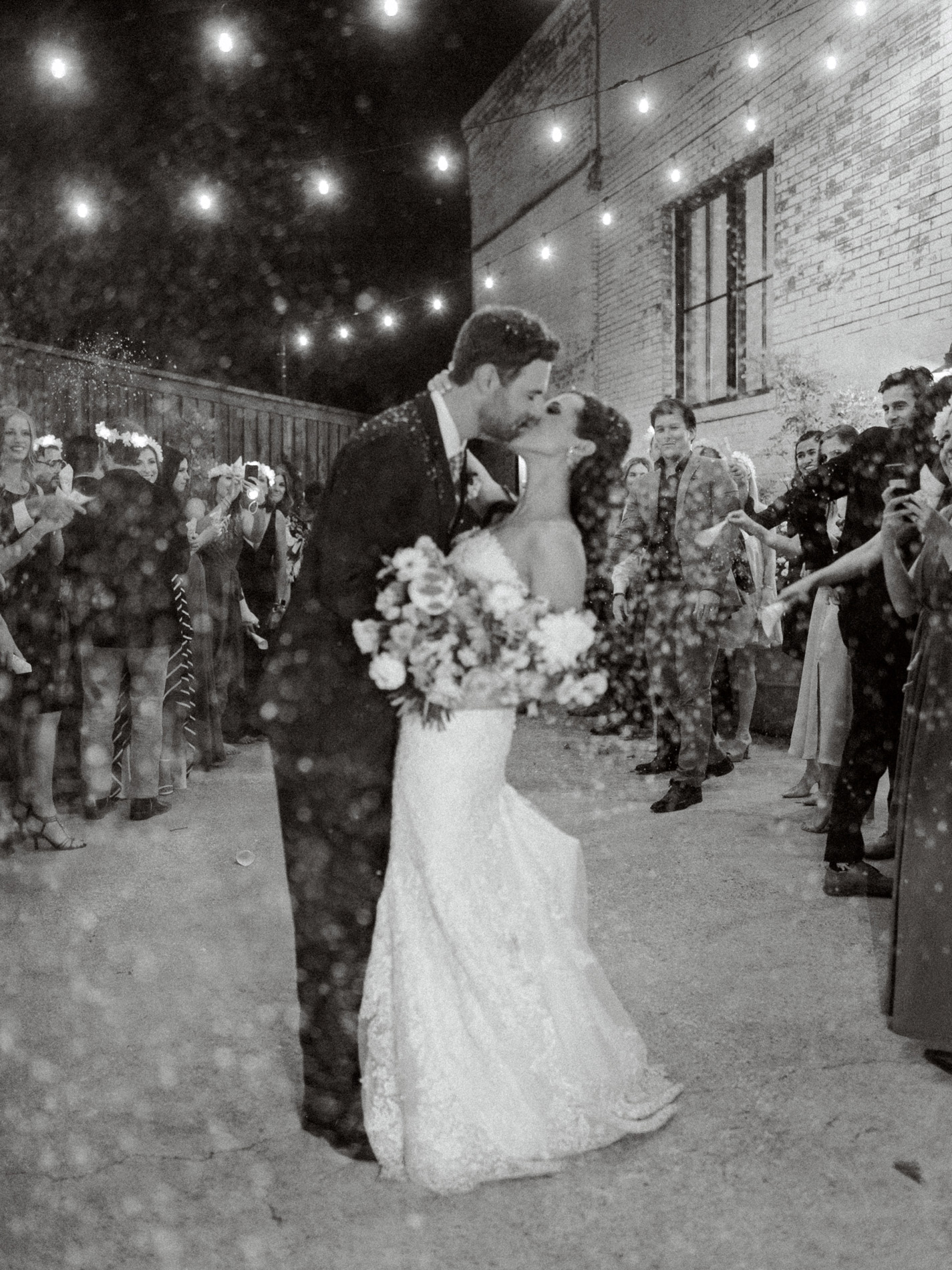 black and white night portrait of bride and groom kissing