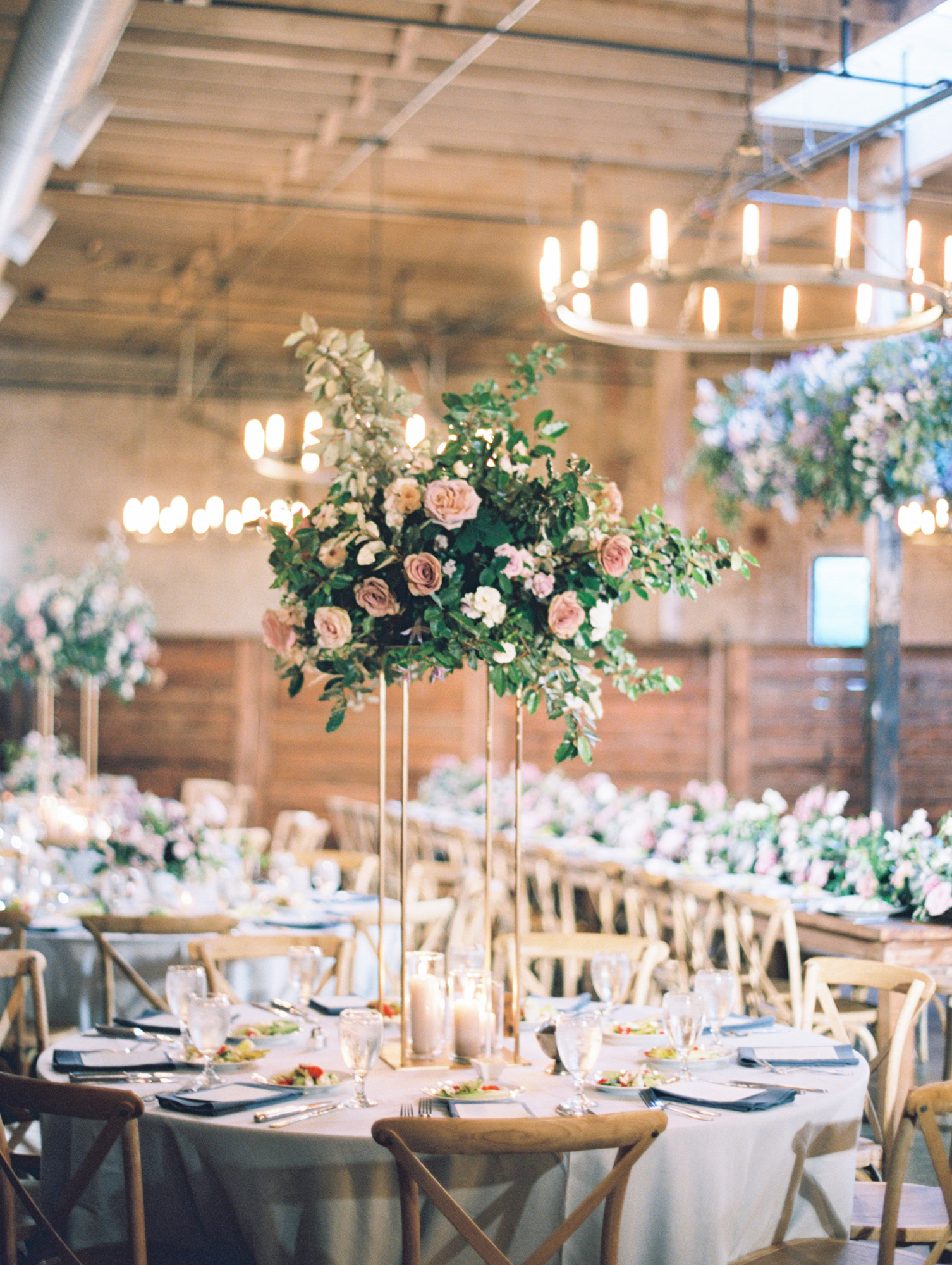indoor reception round tables with tall floral centerpieces
