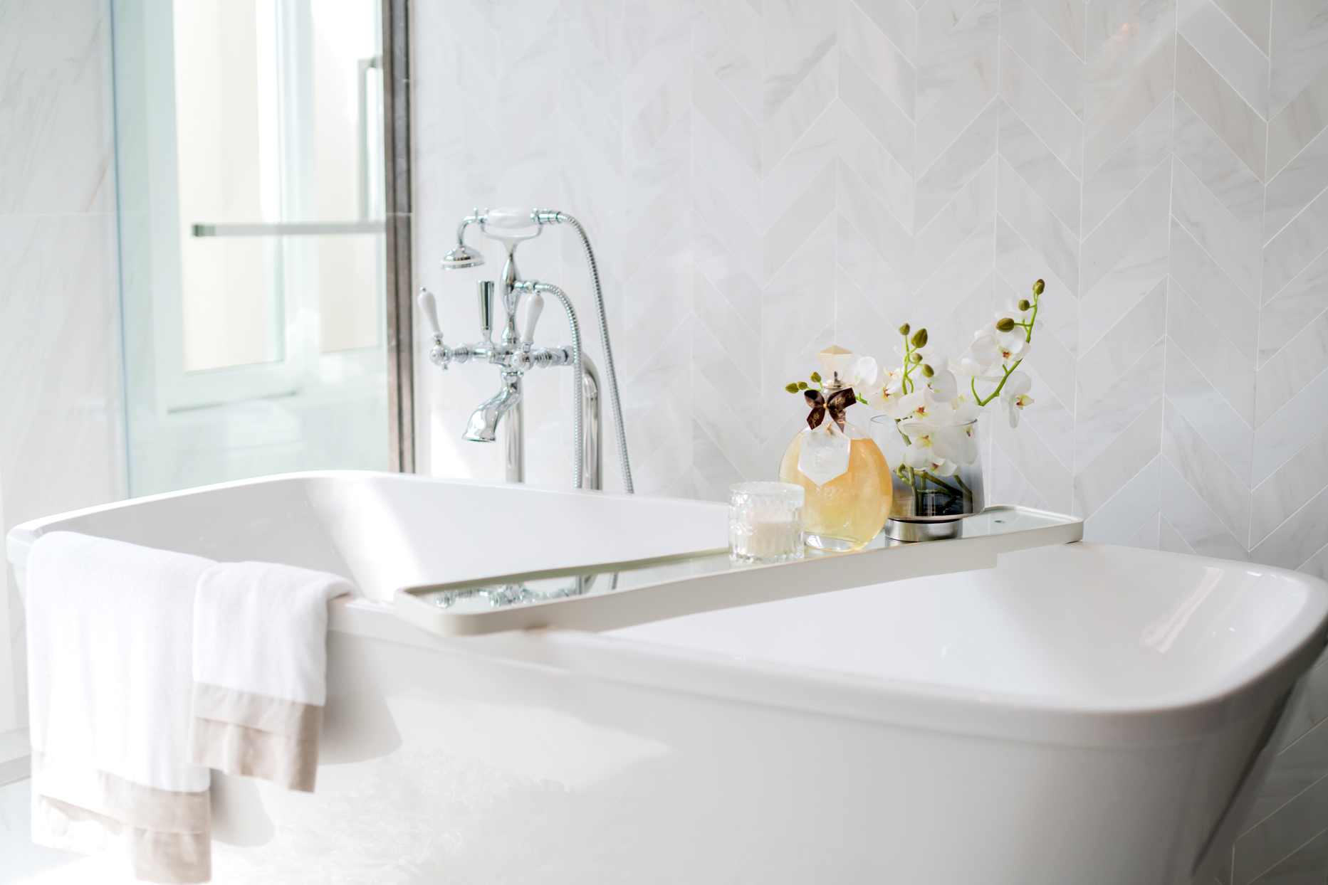 chrome faucet on white bathtub with table and towels
