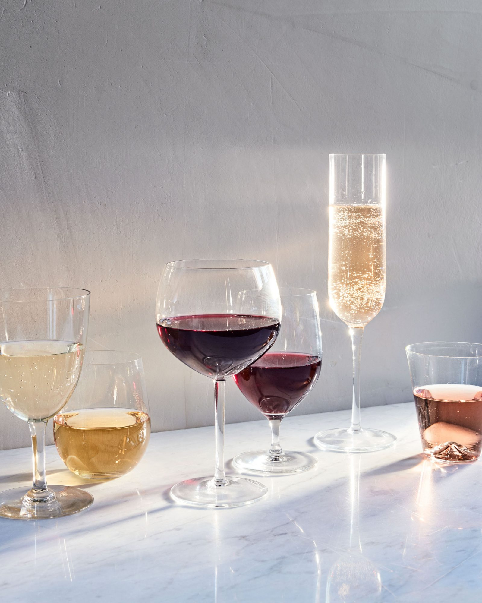 glasses of white wine, rosé wine, red wine, and sparkling wine on a marble surface