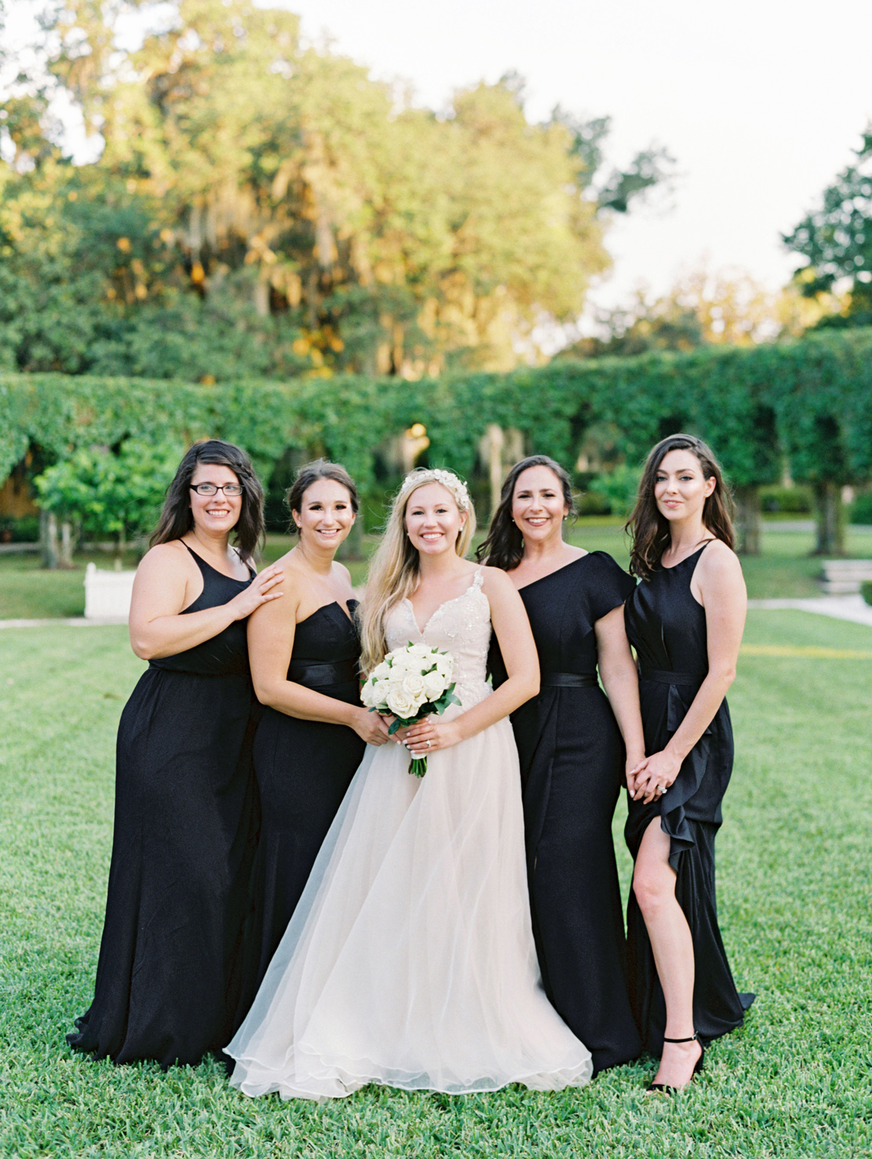 bride with bridesmaids in mismatched black dresses