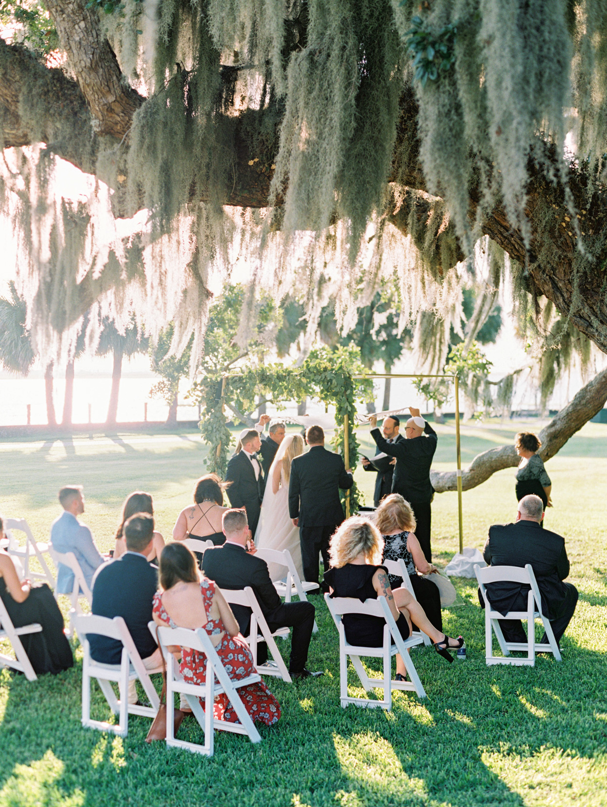 outdoor wedding ceremony with tallit held above couples heads