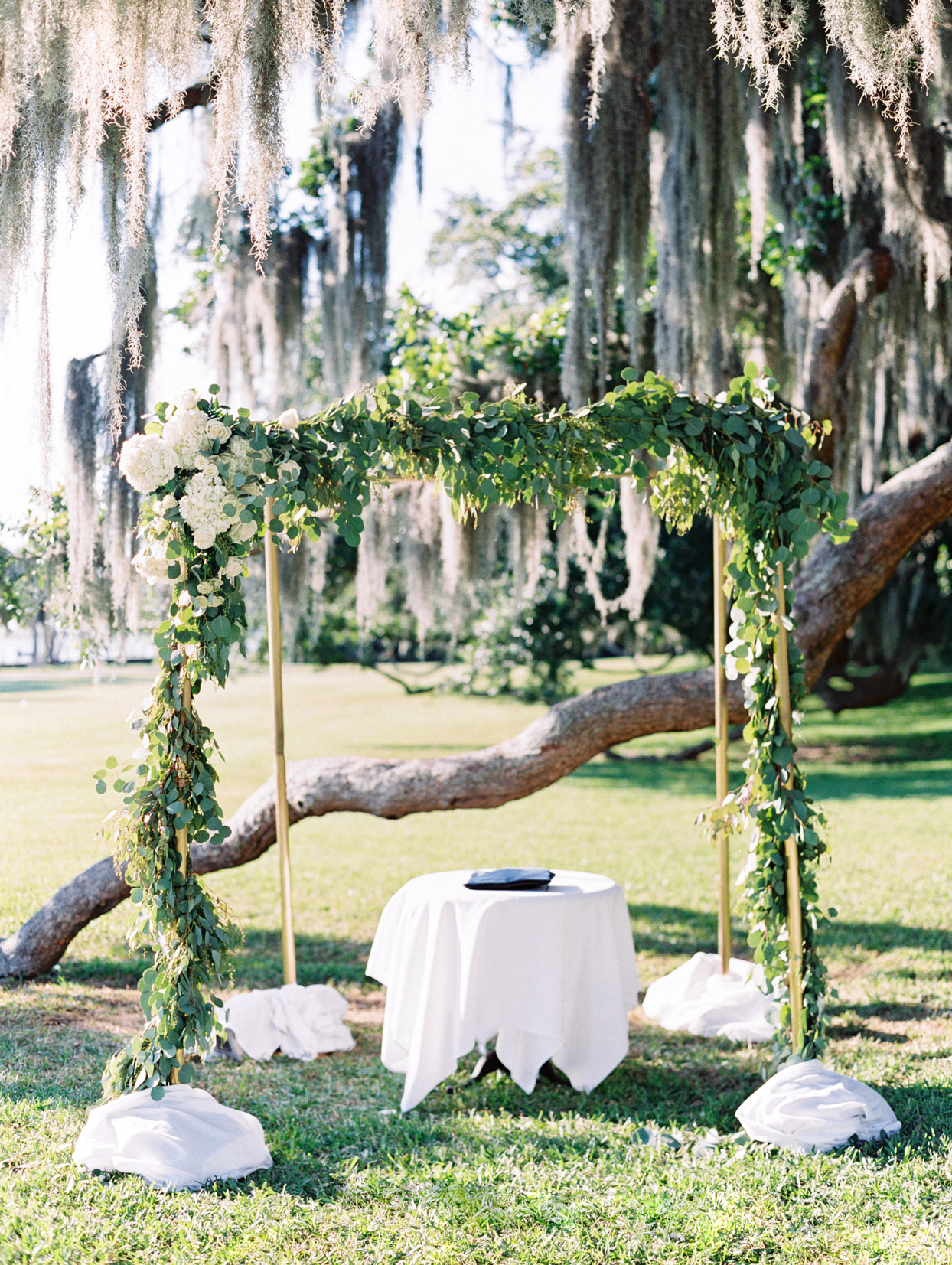chuppah decorated with greenery and white roses
