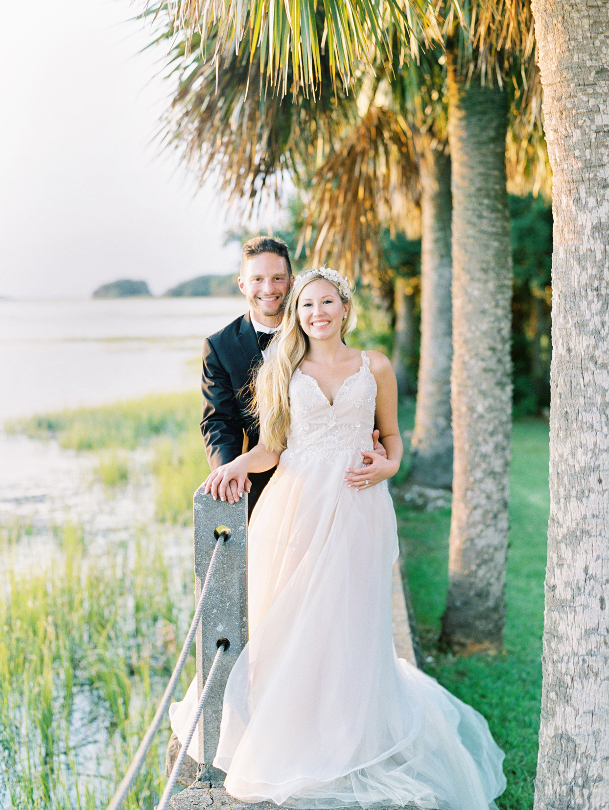 bride and groom posing in front of palm trees