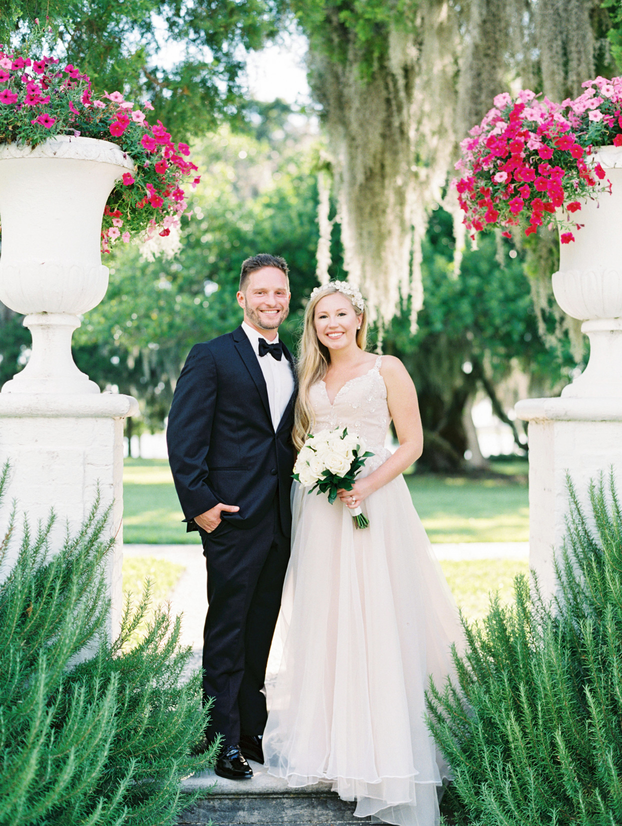 bride and groom standing between planters with pink flowers