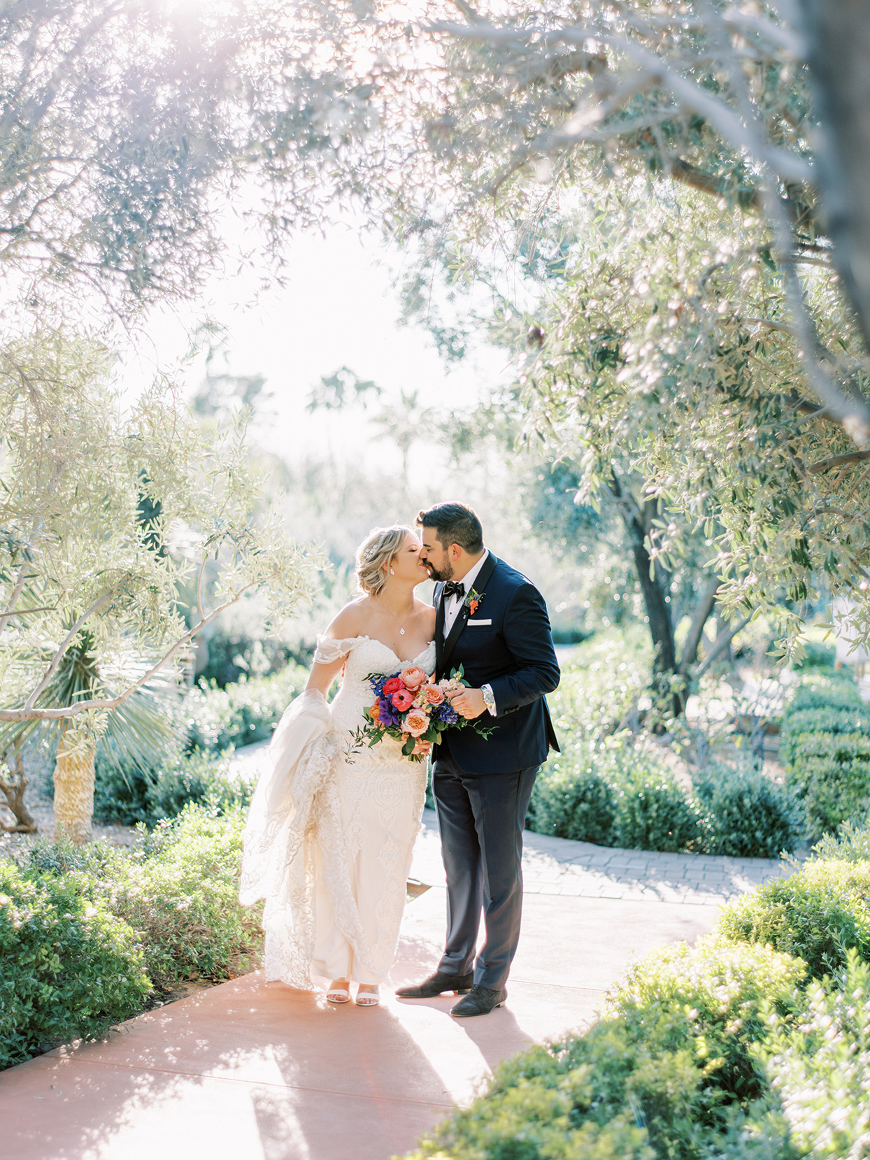 bride and groom share a kiss under trees on outdoor pathway