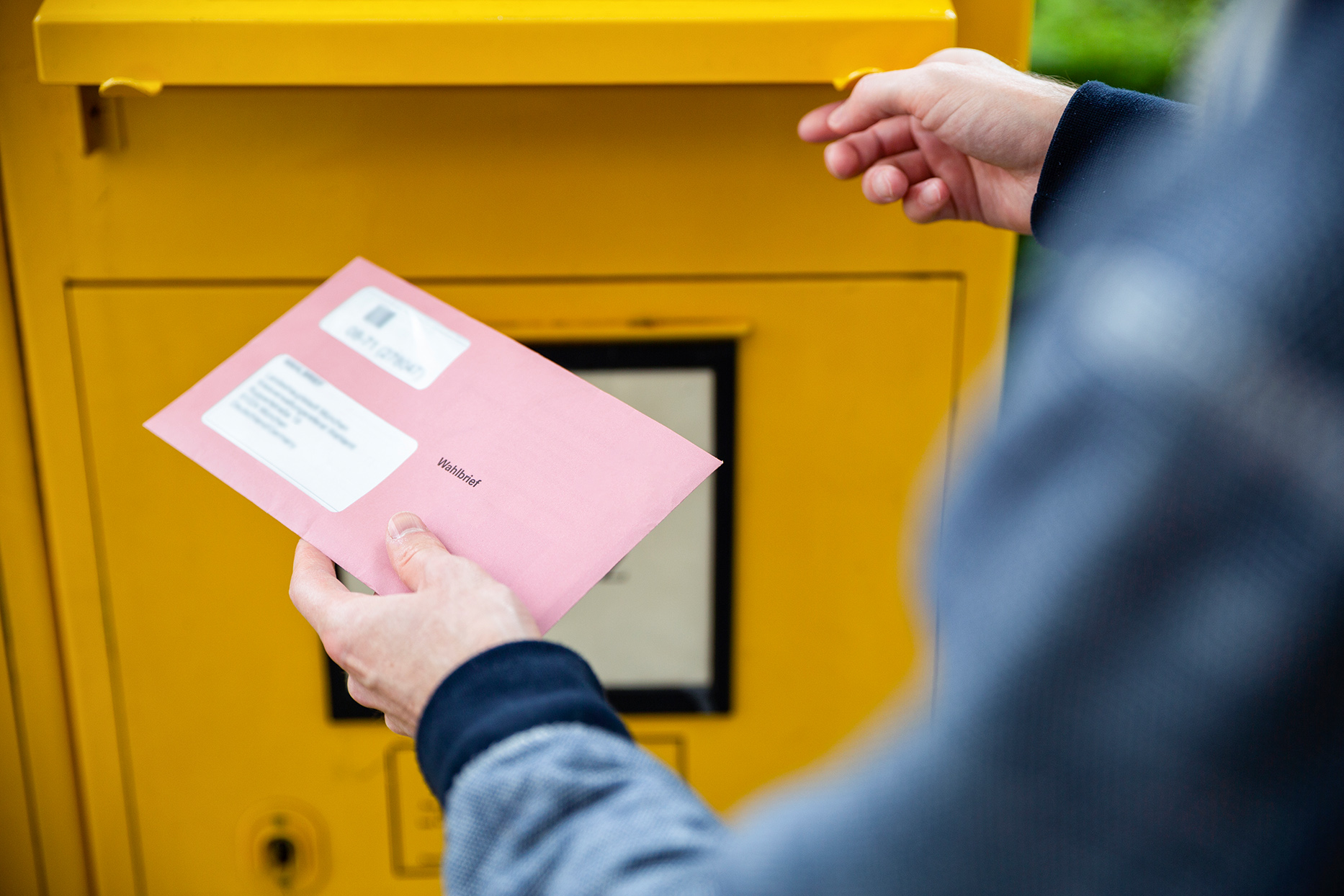 Elector holding documtents for the postal vote in front of the mailbox