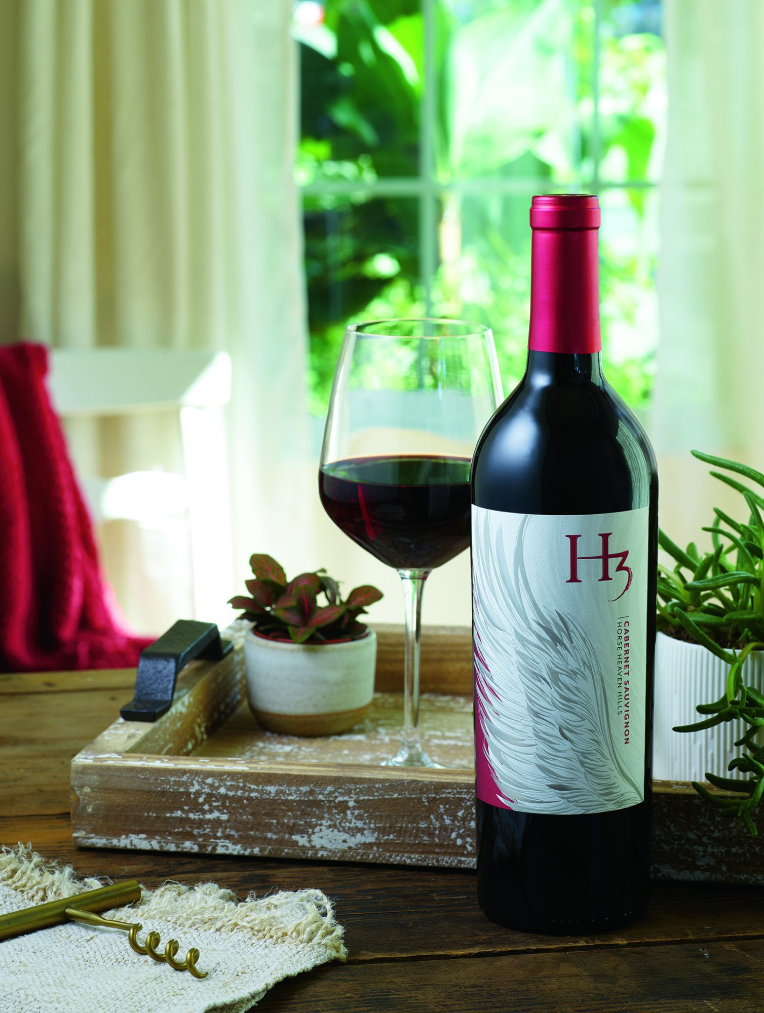 bottle of red wine and glass of red wine on wooden table with corkscrew and other accessories