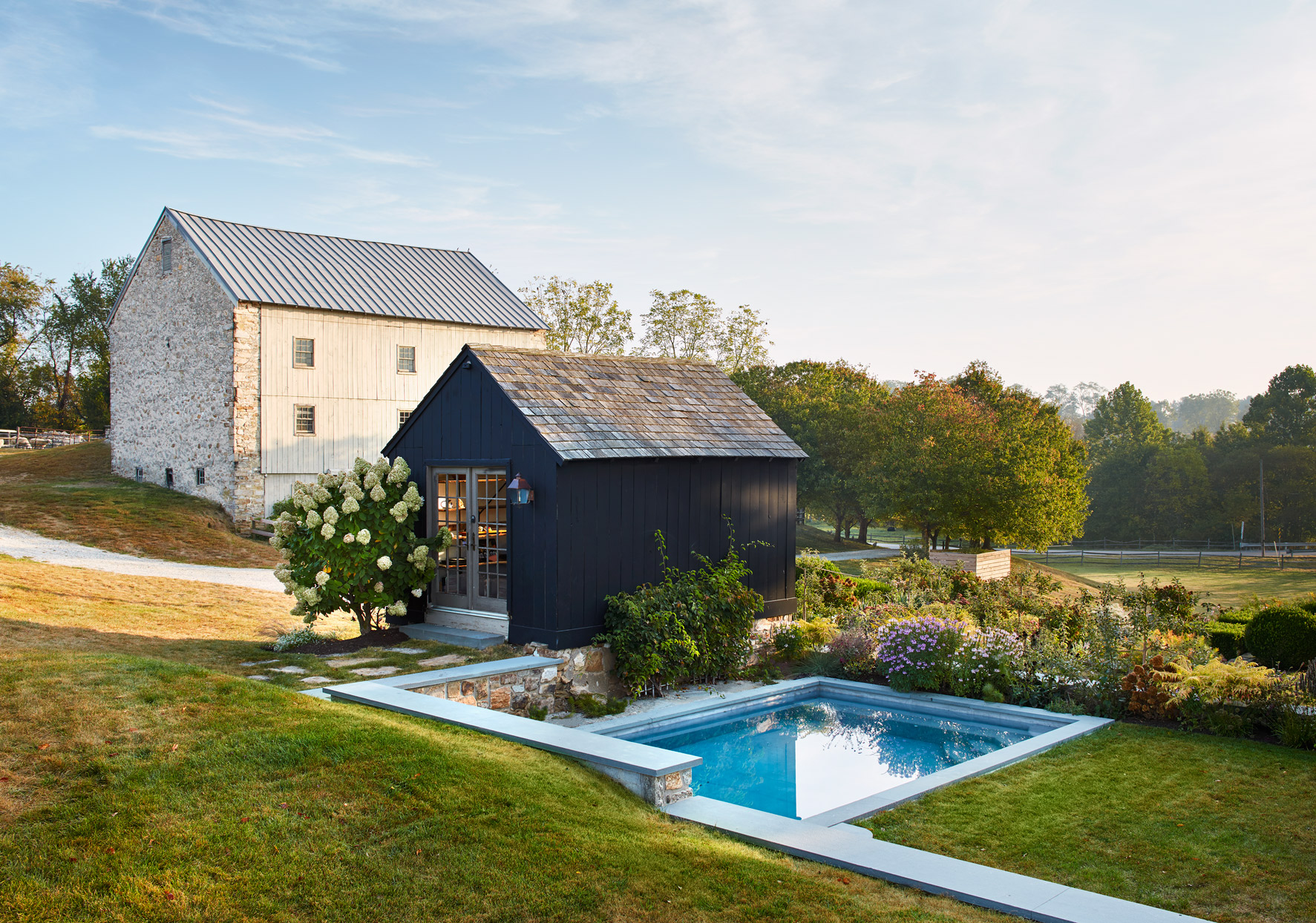 the pool and carriage house landscaped with bright flowers