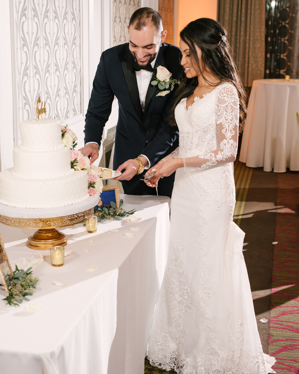 bride and groom cutting cake on gold stand
