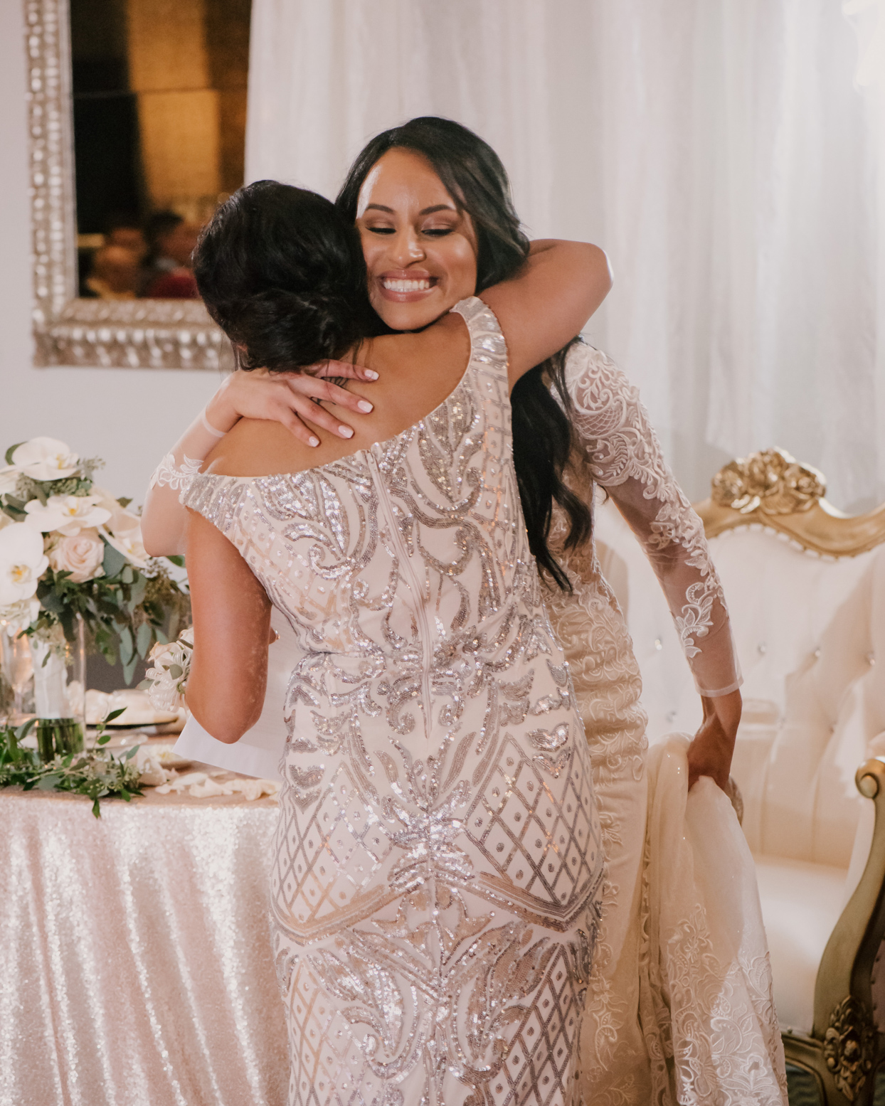 bride hugging mother in gold and white shimmering dress