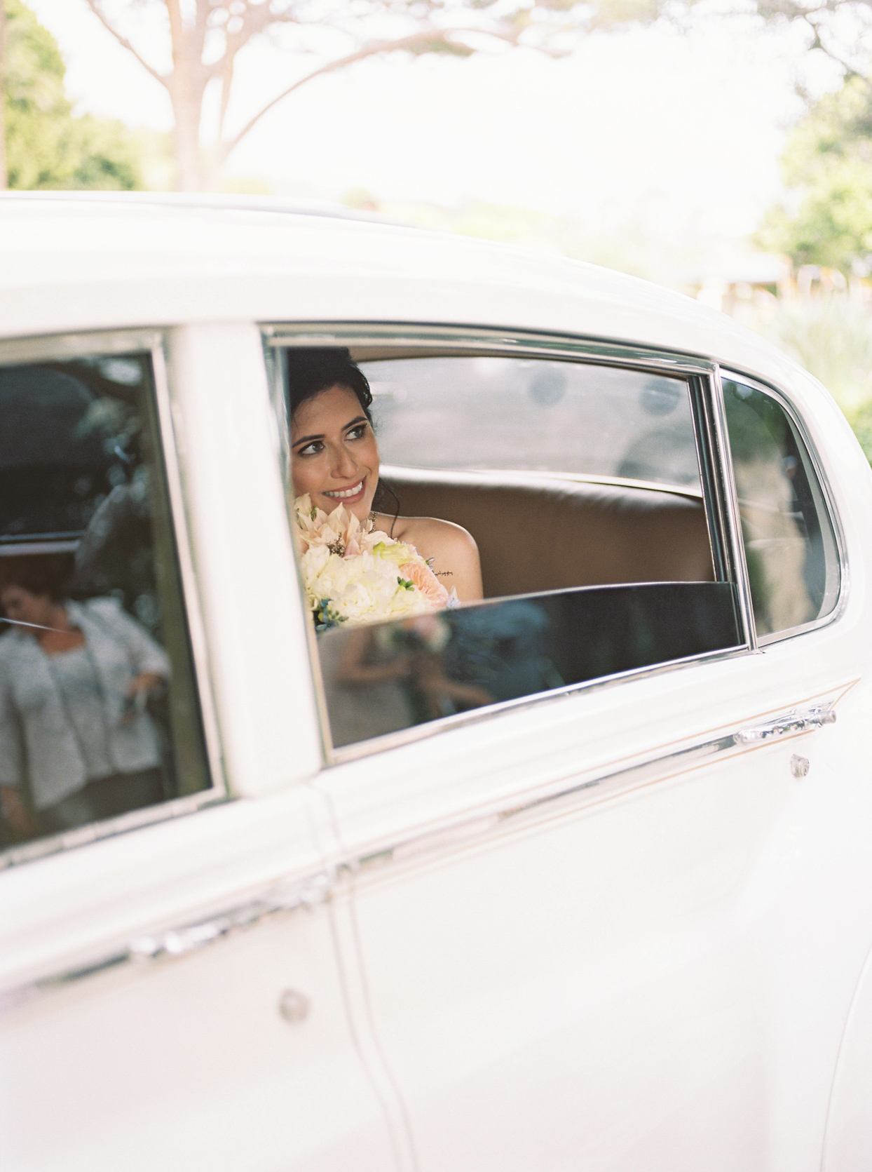 bride smiling out rolled down window of white car