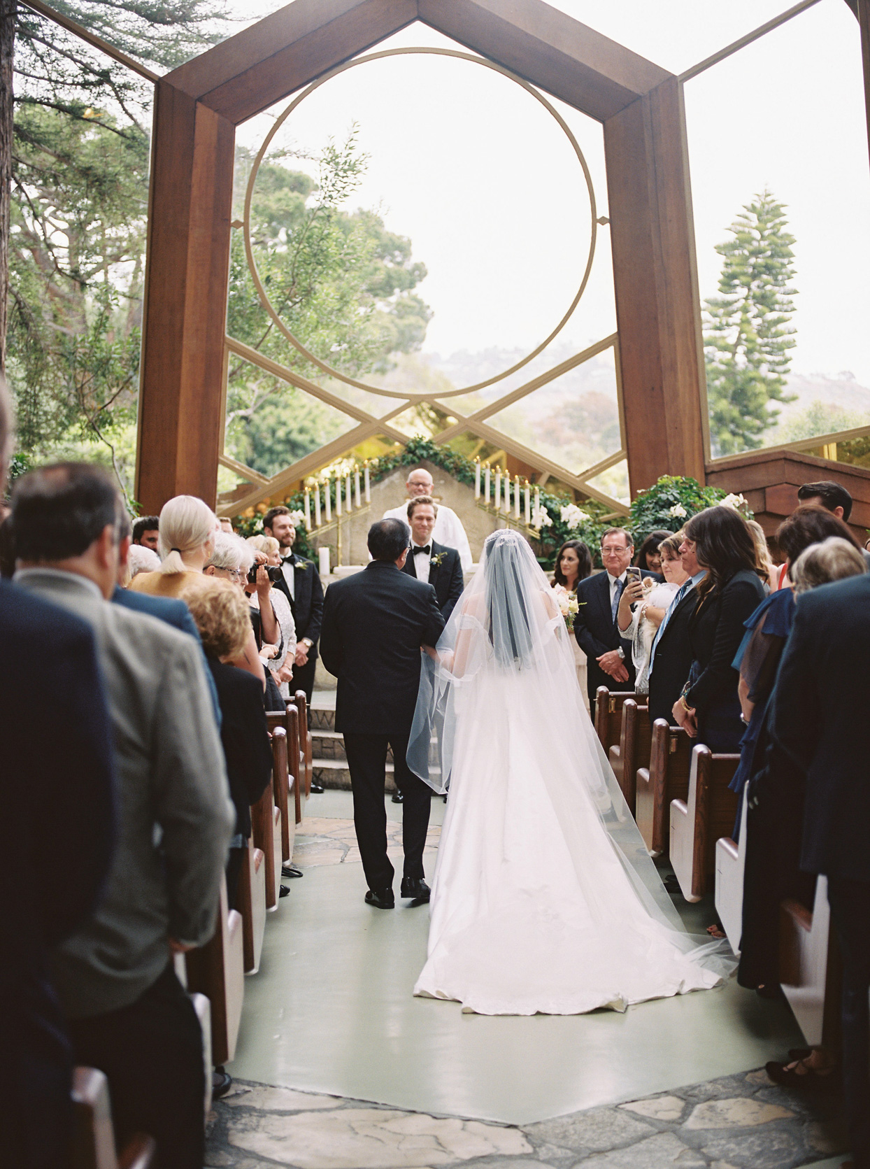 bride and father walking down aisle of church while groom beams